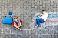 获得两个小孩的男孩与火车图片图画的乐趣与在地面的五颜六色的白垩 免版税图库摄影