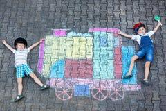 获得两个小孩的男孩与火车的乐趣用粉笔写图片 库存图片