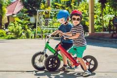 获得两个小男孩的孩子在平衡自行车的乐趣在国家热带路 库存照片