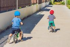 获得两个小男孩的孩子在平衡自行车的乐趣在国家 免版税库存照片