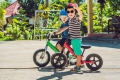 获得两个小男孩的孩子在平衡自行车的乐趣在国家 库存照片