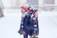 获得两个愉快的小男孩与雪的乐趣 库存照片