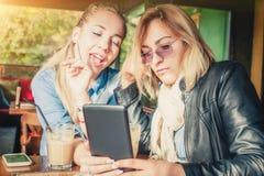 获得两个的女朋友与数字式片剂的乐趣 库存照片