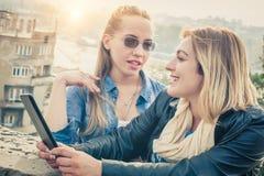 获得两个的女朋友与数字式片剂的乐趣 免版税库存图片