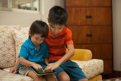 获得两个的男孩与一种数字式片剂的乐趣 免版税库存图片