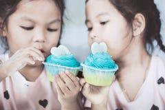 获得两个逗人喜爱的亚裔儿童的女孩吃的乐趣蓝色杯形蛋糕 免版税库存图片