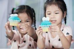 获得两个逗人喜爱的亚裔儿童的女孩吃的乐趣蓝色杯形蛋糕 免版税库存照片