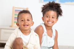 获得两个逗人喜爱的孩子乐趣在家 免版税图库摄影