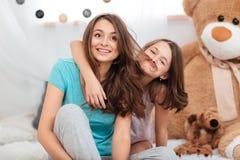 获得两个逗人喜爱的滑稽的姐妹演奏和乐趣 图库摄影