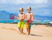获得两个年轻的男孩在tropcial海滩的乐趣 免版税图库摄影