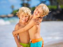 获得两个年轻的男孩在tropcial海滩的乐趣 免版税库存照片