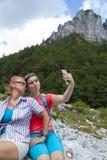 获得两名俏丽的妇女做duckface和拍selfie照片的乐趣在山峰 免版税库存照片