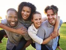 获得两对年轻的夫妇扛在肩上的乐趣户外 图库摄影