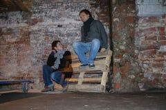 获得两的年轻人乐趣 红砖墙壁背景的人们  免版税库存照片