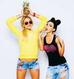 获得两相当白肤金发和深色的女朋友夏天画象乐趣用菠萝,芯片 唱歌与太阳镜 免版税库存照片