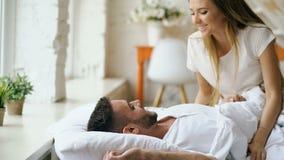获得乐趣亲吻和拥抱他的丈夫的可爱的妇女在床 年轻美好和爱恋的夫妇醒在 股票录像