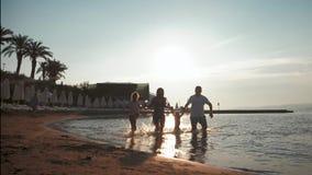 获得乐趣和享受在海滩的活跃家庭剪影统一性在日落 股票录像