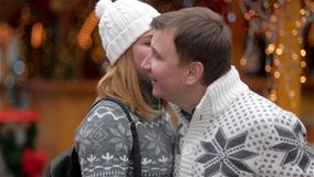 获得乐趣和亲吻在圣诞节市场上的快乐的愉快的年轻夫妇 男人和妇女在上一起花费时间 股票视频