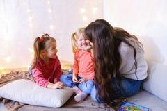 获得乐趣和使用与小女孩的美丽的更老的姐妹 图库摄影