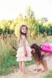 获得乐趣和使用与沙子的两愉快的女孩画象晴朗的夏日 免版税库存照片