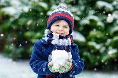 获得乐趣和使用与雪的五颜六色的冬天时尚衣裳的逗人喜爱的矮小的滑稽的孩子男孩,户外在降雪期间 图库摄影