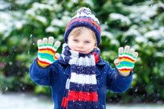 获得乐趣和使用与雪的五颜六色的冬天时尚衣裳的逗人喜爱的矮小的滑稽的孩子男孩,户外在降雪期间 免版税库存图片