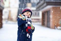 获得乐趣和使用与雪的五颜六色的冬天时尚衣裳的逗人喜爱的矮小的滑稽的孩子男孩,户外在降雪期间 免版税库存照片