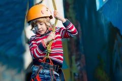 获得乐趣和使用在冒险公园,拿着绳索和攀登木台阶的男孩 库存照片