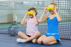 获得乐趣和使用在网球场的孩子 库存照片