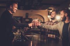 获得乐趣和喝桶装啤酒的老朋友在酒吧柜台在客栈 免版税库存图片