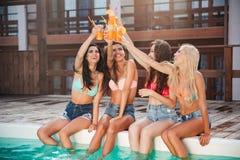 获得乐趣和喝鸡尾酒的四个女孩在游泳池 图库摄影