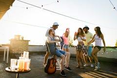 获得乐趣和喝鸡尾酒的朋友室外在屋顶聚会 免版税库存图片