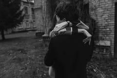 获得乐趣和拥抱在秋天公园的时髦的夫妇 递clos 免版税库存图片