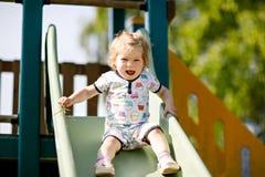 获得乐趣和滑在室外操场的愉快的白肤金发的矮小的小孩女孩 正面滑稽小儿童微笑 库存图片
