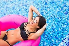 获得乐趣和笑在一个可膨胀的巨型桃红色火鸟水池浮游物床垫的年轻和性感的女孩在比基尼泳装 有吸引力的tanne 免版税库存照片