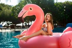 获得乐趣和笑在一个可膨胀的巨型桃红色火鸟水池浮游物床垫的年轻和性感的女孩在比基尼泳装 免版税库存照片