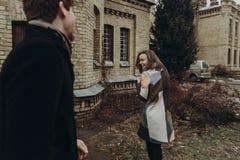 获得乐趣和笑在秋天公园的时髦的夫妇 人和w 免版税库存图片