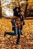 获得乐趣和笑在秋天的有吸引力的愉快的豪华夫妇 库存照片