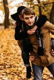 获得乐趣和笑在秋天的有吸引力的愉快的豪华夫妇 库存图片