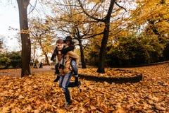 获得乐趣和笑在秋天的有吸引力的愉快的豪华夫妇 免版税库存照片