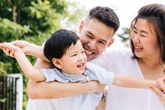 获得乐趣和运载孩子的亚洲家庭在公园 库存照片