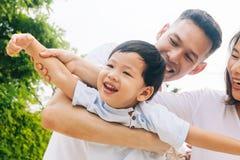 获得乐趣和运载孩子的亚洲家庭在公园 免版税库存照片