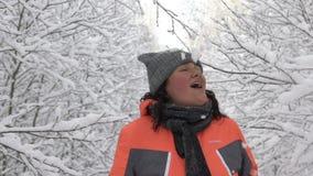 获得乐趣在冬天森林,接触多雪的分支和得到在她的头的滑稽的妇女落的雪,圣诞节 股票视频