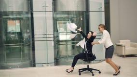 获得乐趣在办公室大厅乘坐的椅子和投掷的文件享受自由和断裂的嬉戏的女孩女实业家 股票录像