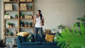 获得乐趣在家听到音乐的可爱的亚裔妇女通过拿着智能手机的耳机,唱歌和 股票录像