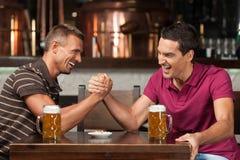 获得乐趣在酒吧。获得两个的朋友喝啤酒和乐趣 免版税库存照片