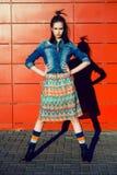 获得乐趣,摆在和微笑在红色墙壁背景附近的年轻少年女孩在裙子和牛仔裤夹克在日落 图库摄影