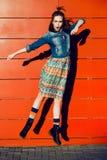 获得乐趣,摆在和跳跃在红色墙壁背景附近的年轻少年女孩在裙子和牛仔裤夹克在日落 免版税库存照片
