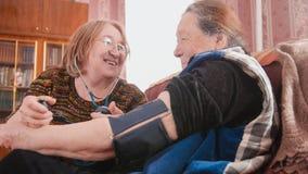 获得乐趣-检查健康状态与测压器-措施压力,领抚恤金者的两个领抚恤金者-资深夫人 库存图片