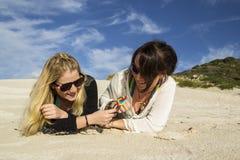 获得二个的少妇在海滩的乐趣 免版税图库摄影